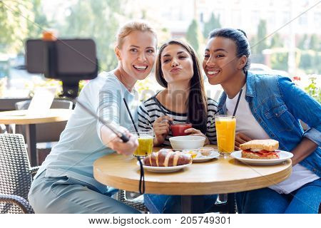 Incredibly photogenic. Three upbeat young women sitting on the terrace of a cafe and posing while one of the friends taking a selfie with them using a monopod