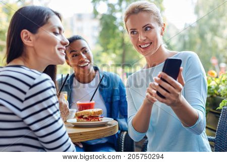 Check these out. Merry young woman showing the photos from her last vacation on her phone to her best friends while having lunch with them in a cafe