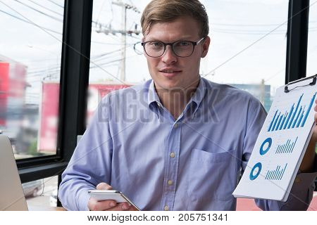 Businessman Shows Financial Graph Diagram At Office. Young Man Present Investment Chart At Workplace