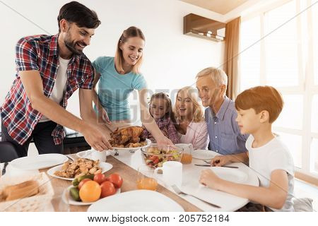 The family sits down for dinner on Thanksgiving. The man serves a festive turkey, his wife stands beside him and serves a salad, the rest sit and look forward to