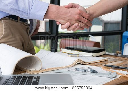 Engineer Handshaking For Successful Deal In Construction Plan. Architect Shake Hand For Agreement In