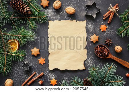 Santa wishlist or Christmas letter background concept: holiday decorations, fir tree, spices, stars and cookie cutters with blank paper for text . Top view, horizontal