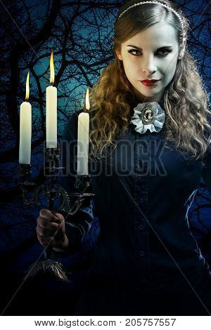 Beautiful witch in a gothic dress with a candlestick