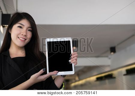 Businesswoman Hold Digital Tablet At Workplace. Young Woman Shows Information In Touchpad At Office.