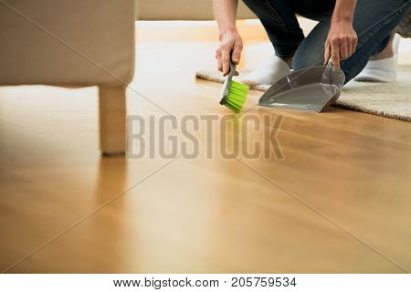 Person Using Brush And Dustpan