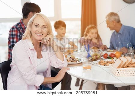 The family eats for Thanksgiving. A woman is sitting in the foreground at a table with everyone. She is posing smiling. Family sitting and eating