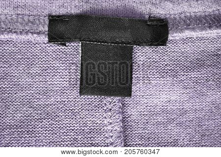 Blank textile clothes label on violet knitted background closeup
