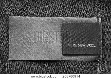 Textile clothes label lettered pure new wool on black wool background