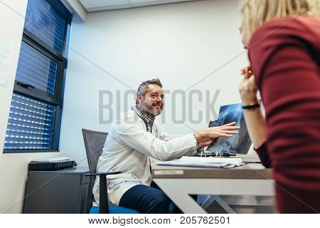 Doctor discussing medical scan result with patient. Medicine practitioner with x-ray talking to a woman in clinic.