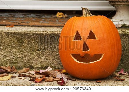a jack o lantern at the steps of door.