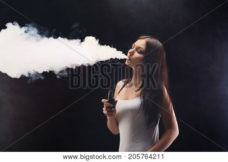 Girl with vaping at black studio background. Young woman smoking e-cigarette to quit tobacco. Vapor and alternative nicotine free smoking concept, copy space