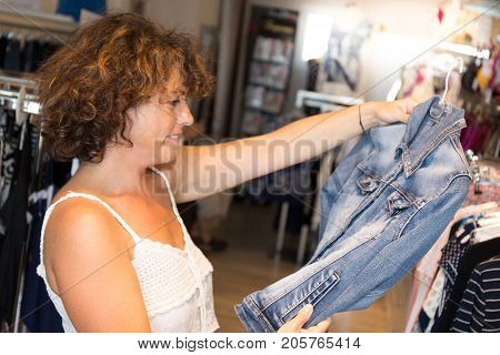 Forties Woman Looking Through New Clothes During Shopping