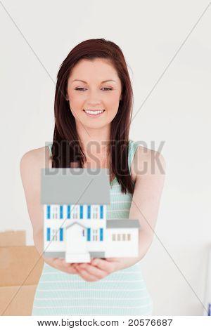 Gut aussehende Rothaarige Frau gedrückt halten ein Miniatur-Haus und auf dem Boden stehend
