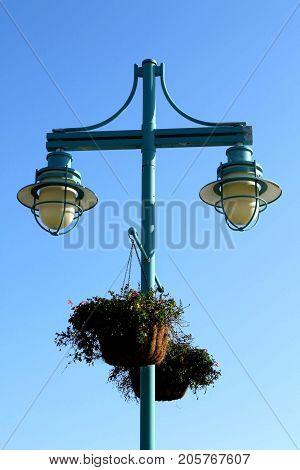 Fancy street lighting and flower baskets set against bright blue skies.