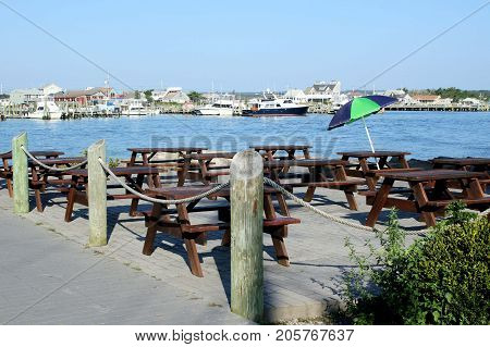 Large group of picnic tables and one umbrella on the edge of a busy port channel.