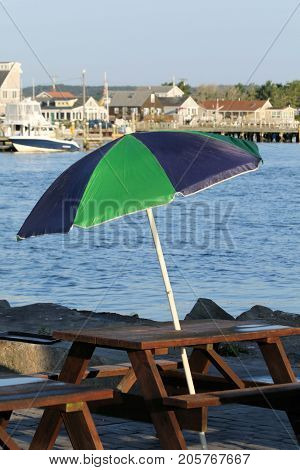Black and green beach umbrella mounted on a picnic table on the shoreline of a channel on a sunny summer day.