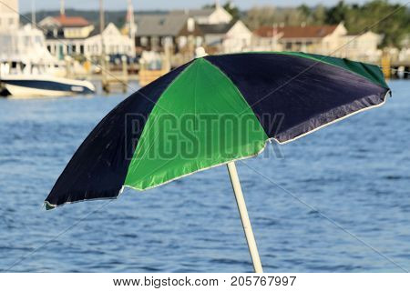 Black and green beach umbrella on the shore of a boat channel.
