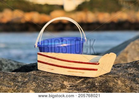 Close-up of sand pail and toy rowboat sitting on a rock jetty on a summer day.