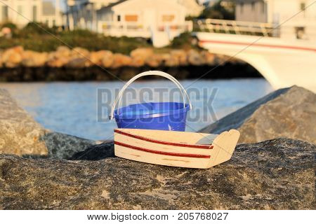 Wooden toy rowboat and sand pail sitting on a rock jetty.