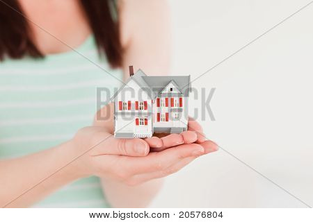 Frau hält ein Miniatur-Haus stehen