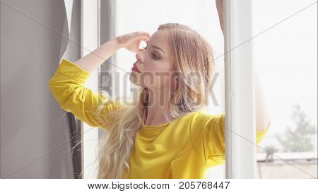 Attractive female in a yellow dress with long hair stands by the window and holds her hand over the window frame