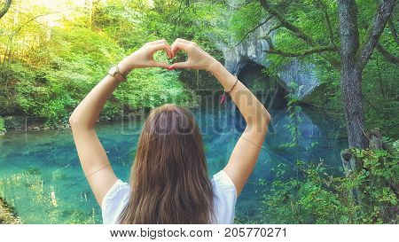 Young woman holding heart-shape for the beautiful nature.