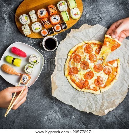 Pizza and sushi rolls and hands take food. Food background. Flat lay, top view.