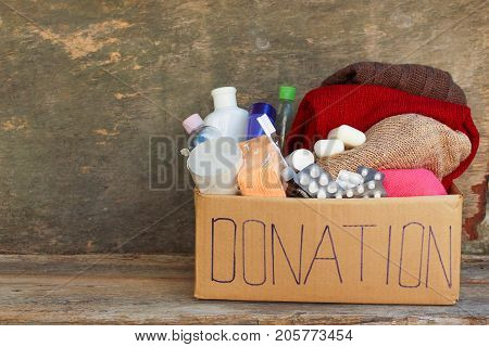 Donation box with clothes, living essentials on wooden background