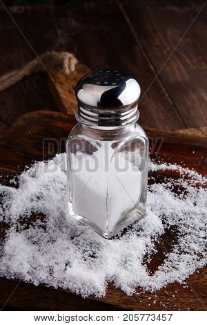 Salt Shaker and salt on wooden table.