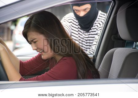Robber holding a gun for robbery car owner /Screaming woman /Criminal and car thief concept