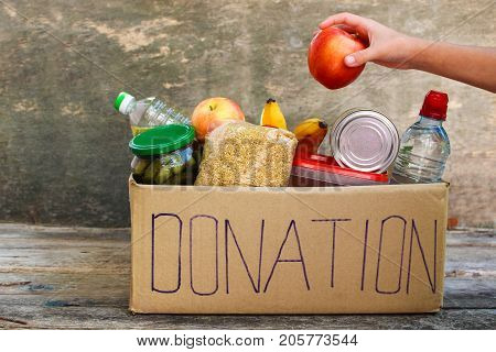 Donation box with food on the old wooden background.