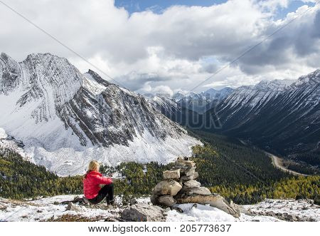 Woman resting at Arethusa Cirque in Alberta (Canada) and enjoying the mountain view.