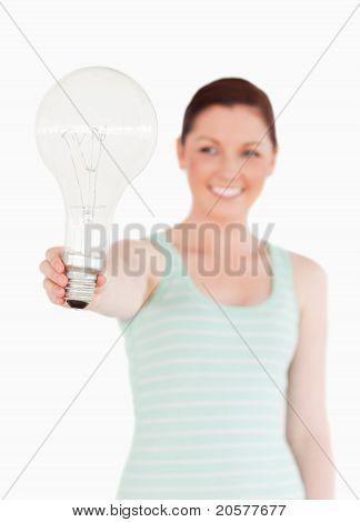 Ziemlich Rothaarige Frau hält eine Lampe stehen