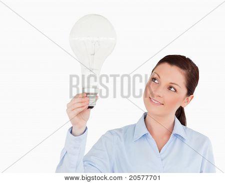 Wunderschöne Rothaarige Frau hält eine Glühbirne stehen