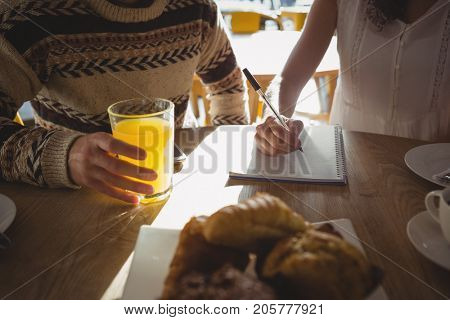 Mid section of woman with man writing on book while sitting at table in cafe