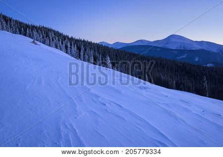 Winter Landscape Of Mountains With Snow At The Foreground And A Mountaun Range At The Background.