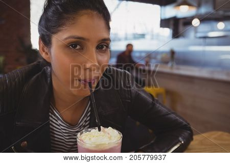 Portrait of young woman drinking milkshake at cafe