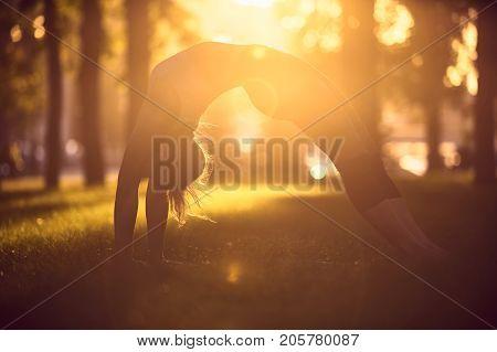 girl is doing yoga, standing in bridge wheel pose urdhva dhanurasana in the park with sunset on background
