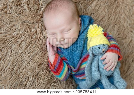 Little kid wrapped in a blue scarf with a gray toy hare resting, topview