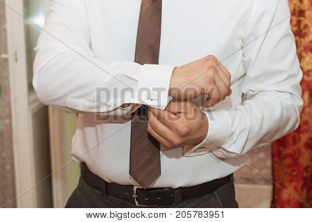 man buttons shirt a man in a white shirt morning groom hands of a man close-up a white shirt on a businessman man buttons shirt sleeve businessman puts on a suit