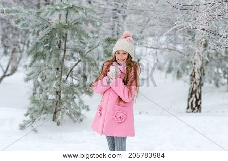 Adorable smiling girl playing with the snow in the winter snow-covered woods
