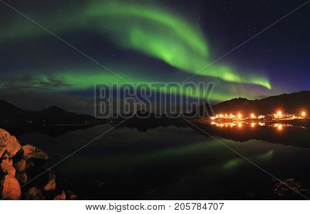 Green northern lights in night starry sky. Northern lights reflect in lake in small norwegian resort town. Beautiful north night lanscape.