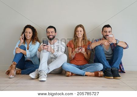 Group of friends using smartphone, sitted on floor