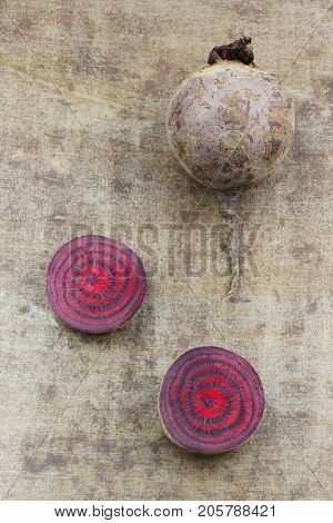 freshly harvested red beet root and some cut slices on a grungy metal background