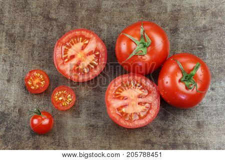 Whole and cut tomatoes and cherry tomatoes on a grungy metal background