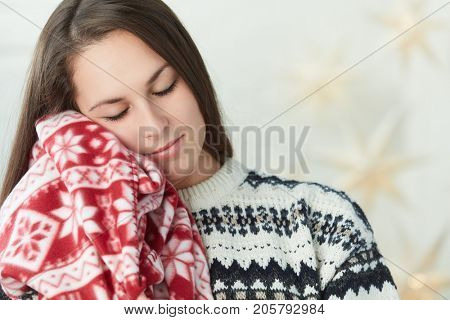 Pretty woman with warm blanket and closed eyes, winter portrait.
