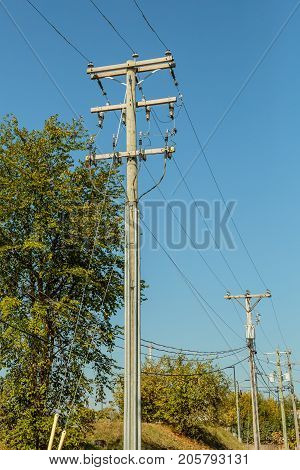 Utility posts for phone electricity and cable under a blue sky