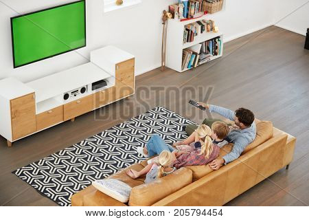 High Angle View Of Family Sitting On Sofa In Lounge Watching TV