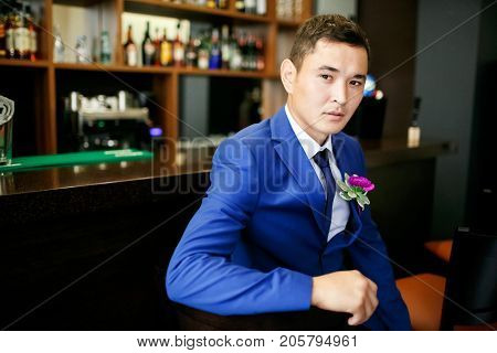 The groom in a blue suit is sitting in a bar with a buttonhole on his lapel, a portrait of a handsome man.