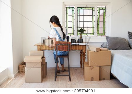 Woman In Bedroom Running Business From Home Dispatching Goods